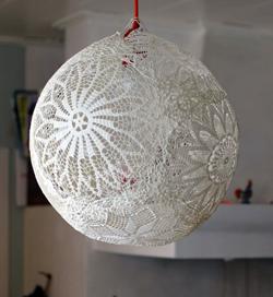 Färdig lampa. Klot av spetsdukar som lampskärm, upphängd i en röd sladd.
