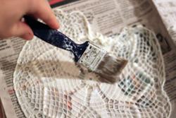 Målar klister på en spetsduk med pensel